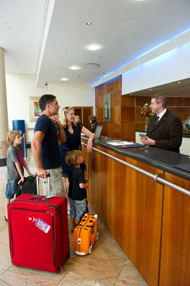 Des touristes au comptoir dun hotel | Photo de Holiday Extras