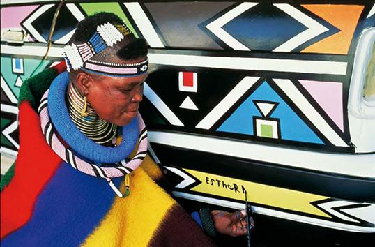 Esther Mahlangu signe la BMW qu'elle vient de peindre.