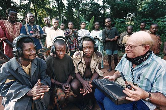 Simla Arom fait écouter                d'anciens enregistrements aux Pygmées Aka en 2001. | Photo                par Harald Schmitt