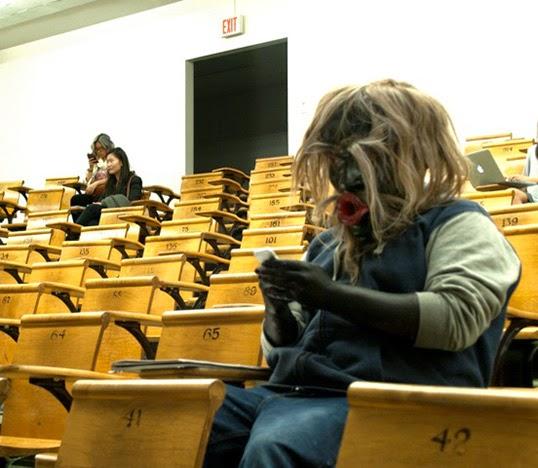 Dzunukwa in Class : photo de Cole Speck montrant un homme dans une salle de cours portant un masque sculpté par Beau Dick.